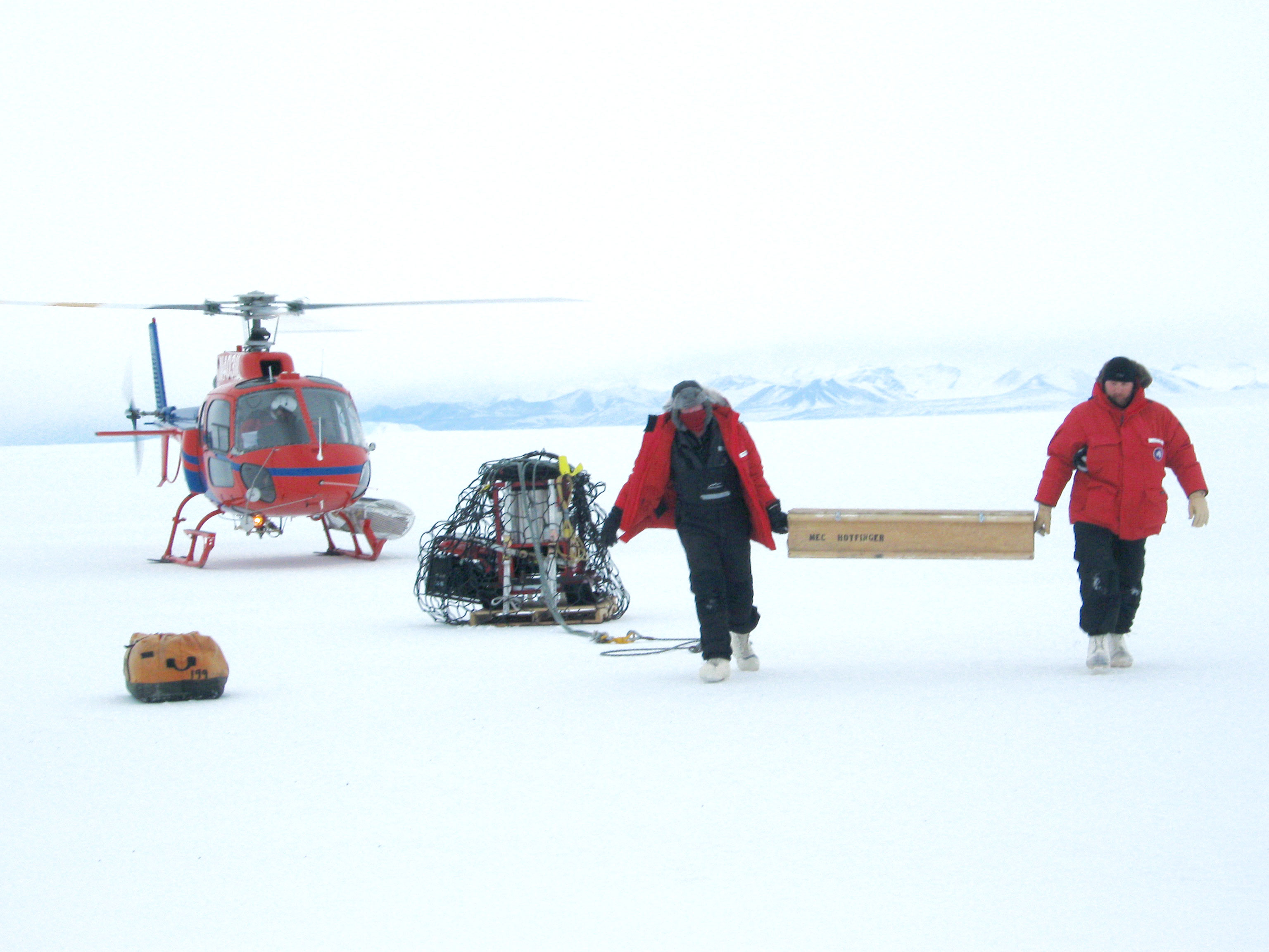 Two researchers just got out an helicopter landed on ice of Antarctica