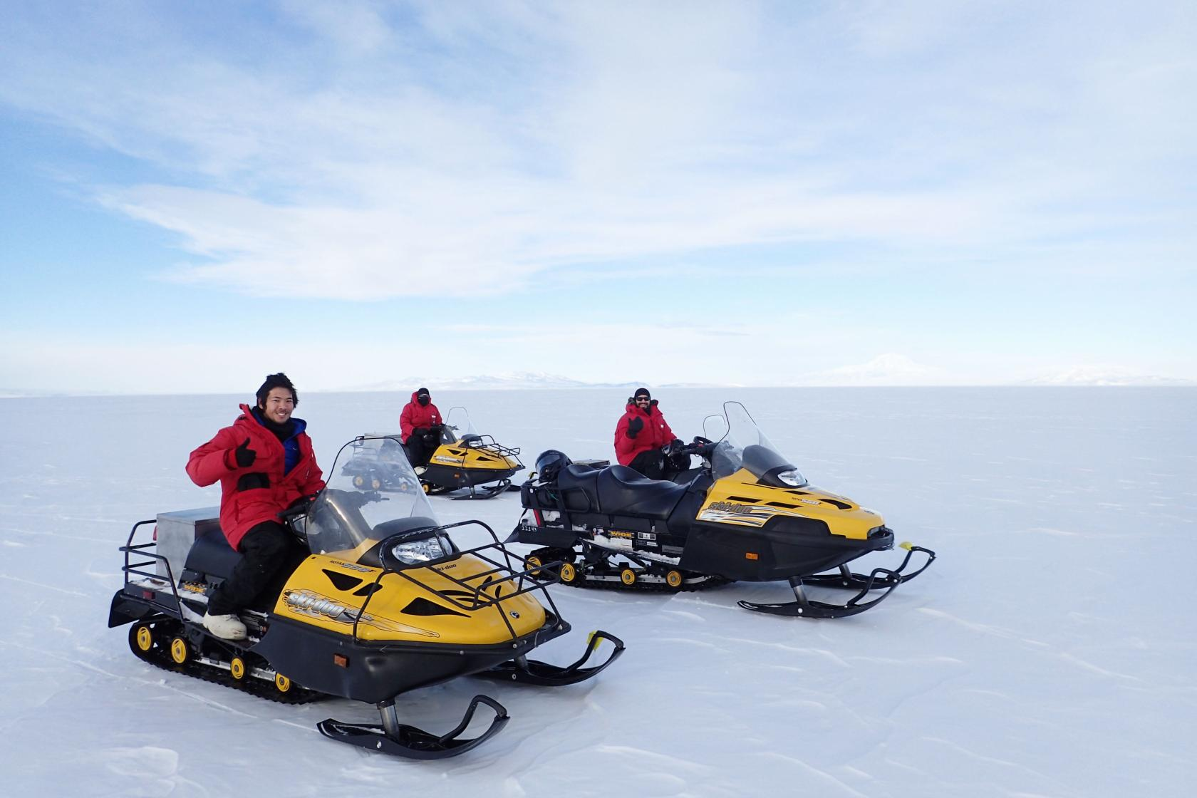 Three students of the Hofmann lab riding snowmobiles in Antarctica